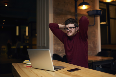 Young handsome male football fan in eyewear and casual wear watching streaming video of match cheering for team feeling disappointed of bad game of players Stock Photo