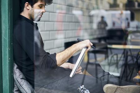 koncentrovaný: Oříznutý obraz úspěšného podnikatele pracujícího na dálku a vytváření nového finančního plánu pro společnost sedící v interiéru kavárny a propagační zázemí pro inzerci