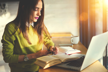 concentrate: Talented female student of journalism creating article for homework using textbook  writing down ideas into copybook sitting in coworking space with laptop