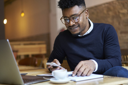 Portrait of smiling afro american blogger checking mail on mobile phone sitting in coffee shop with modern technology. Cheerful stylish hipster guy preparing for upcoming exams and looking on camera Reklamní fotografie