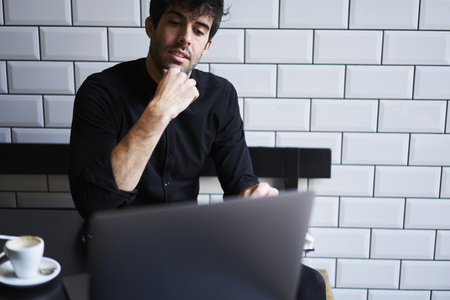 Successful entrepreneur thinking on business plan for his clients sitting in coffee shop with free wifi.Handsome owner watching interesting movie on modern computer with 4G internet connection