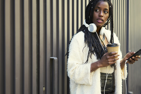 earbud: Afro american female blogger installing mobile application with media player on smartphone.Stylishly student with  headphones messaging with friends.Copy space area for advertising text message