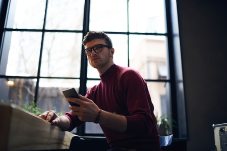 Handsome young hipster guy in spectacles hold smartphone checking wifi connection in coworking space, concentrated young male student chatting with friends in social networks via phone sitting indoors Banco de Imagens