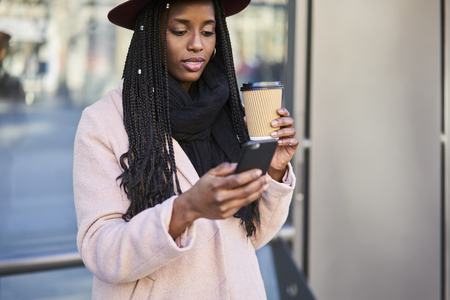 Charming afro american woman with cornrows chatting with friends in social networks and surfing on internet websites for  on mobile phone standing on stop bus Stock Photo