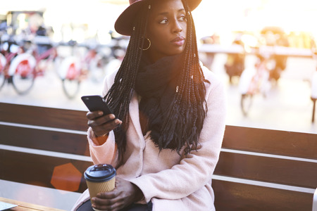 流行に敏感な若い女の子手においしいコーヒーと木製のベンチに座っているとよそ見。女性ブロガーの通りに無料の 4 G 接続を使用して携帯でインタ
