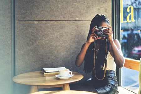 Afro american female traveller making photo of cafe interior on vintage camera sitting at wooden table with diary for interesting places and cup of tasty coffee.Copy space for your advertising area