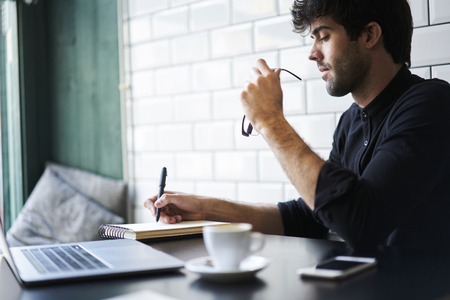 Young concentrated hipster guy creating article for personal website.Intelligent  bearded male preparing for upcoming quality control testing and solving problems writing report analyzing information Stock Photo