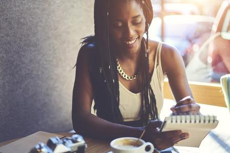 Vrolijke getalenteerde vrouwelijke schilder tekening portretten van bezoekers in coffeeshop in notebook terwijl u geniet van vrije tijd in cafetaria interieur. Lachende jonge vrouw schrijven records indrukken van nieuwe stad Stockfoto