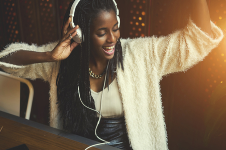 Young cheerful hipster female in casual wear listening music via big white modern headphones, afro american teen girl recreate while enjoying favorite songs from playlist sitting in cafe indoors Фото со стока