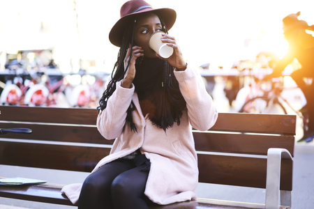 Attractive afro american female designer talking on smartphone with partner about new fashion collection while drinking aroma coffee during break and enjoying sunny day
