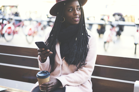 Smiling afro american female student with good mood checking mail on modern mobile phone and enjoying tasty coffee sitting on street during free time and Stock Photo