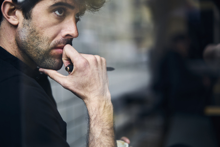 conceived: Cropped image of thoughtful handsome businessman with hand on beard seriously thinking on creation of new building project during free time on promotional background Stock Photo