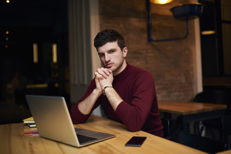 Portrait of handsome male journalist looking at the camera while creating article using laptop computer and free wireless connection, attractive hipster guy preparing homework task in coworking space