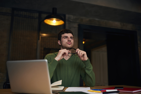 Confident handsome male proud CEO thinking about plans for startup project sitting in coworking space, young student creating report home task using laptop computer and wifi connection in library
