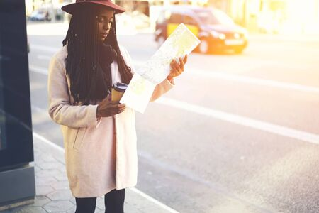 appointed: Afro american female tourist dressed in style hat and pink coat searching right direction on map to getting to appointed place in new town.Young traveller walking on streets of city with coffee
