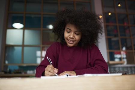 肯定的な集中アフロ アメリカ女子学生文学大学図書館、ペンでアイデアを指摘し才能のあるジャーナリストの作成記事で座っている作文を書く宿題 写真素材