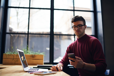 Handsome young male student reading notification on smartphone while preparing homework in coworking space using modern technology and wifi connection,hipster guy using application on cellular indoors