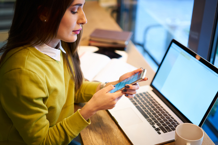 Concentrado exitoso propietario femenino de corporación comercial chateando con ejecutivo mientras hace trabajo remoto a través de la computadora portátil con pantalla en blanco conectado