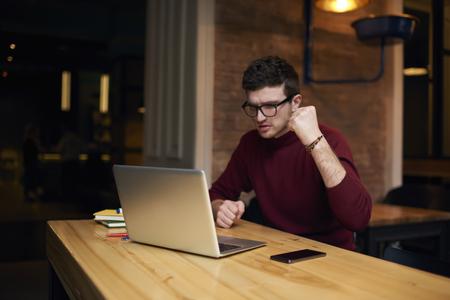 트렌디 한 안경을 입은 잘 생긴 남성, 랩톱 컴퓨터를 통한 축구 경기의 번역 스트리밍 비디오 시청 및 인터넷 연결