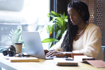 Concentrated afro american  freelancer with cornrows typing on keyboard of modern laptop text information in internet websites for searching ideas and Stock Photo