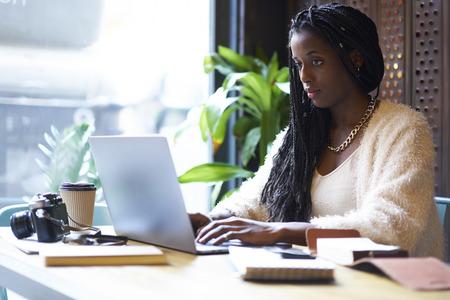 Geconcentreerde afro Amerikaanse freelancer met cornrows die op toetsenbord van moderne laptop tekstinformatie typen in Internet-websites voor het zoeken van ideeën en Stockfoto