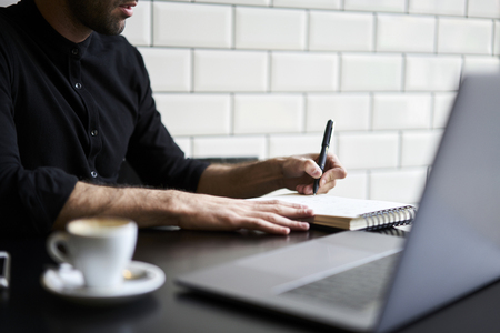 Cropped image of attractive student in casual wear preparing homework making research using internet sources.Professional journalist writing article for publication in magazine sitting indoors