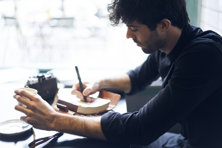 Cropped image of male experienced speaker writing important enter speech for presentation of new book of famous author about travel in coworking place.Copy space area for your advertising text message