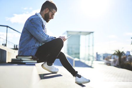 Young talented male student journalist in casual look finishing his home task during break writing composition inspiring by sunny weather Stock Photo - 79986885