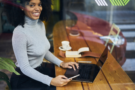 Cheerful skilled female freelancer making remote job testing program made by IT developers happy about having opportunity to work in modern cafe interior Imagens