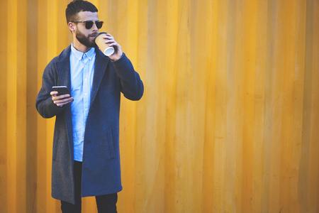 外でコーヒーを飲みながらスマート フォンで「ナビゲーター」アプリケーションを使用して右方法見つけるアイウェアでトレンディな服流行に敏感 写真素材