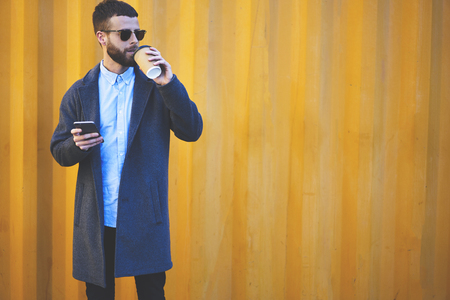 Trendy dressed hipster guy in eyewear drinking coffee outside while using navigator application on smartphone to find right way