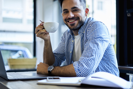 Portrait of smiling skilled programmer enjoying lunch break drinking hot coffee inspiring by  good weather getting ready for working hard