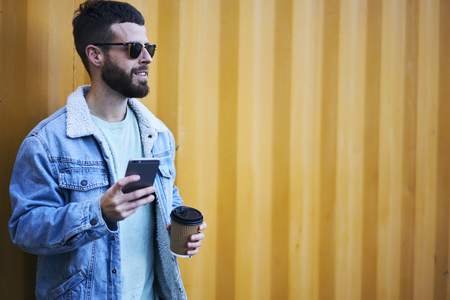 Handsome male hipster in eyewear strolling on city street on vacation trip blogging site motivating followers to travel sharing photos from tour