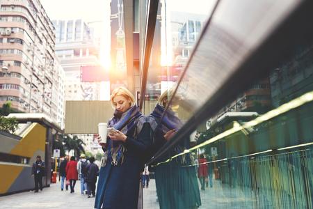 Une jeune fille branchée élégamment habillée utilisant des cartes en ligne en voyage d'affaires pour trouver le chemin du quartier de la société en train de boire du café pour se réchauffer