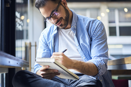 Concentrated male creative artist in trendy glasses inspiring by good atmosphere in cafe drawing illustration for popular newspaper making sketch in personal diary