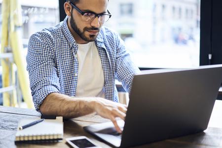 集中して男性 IT プログラマー現代のラップトップ コンピューターを使用してテストするため彼のフォークを送信するデジタル デバイス用の新しい 写真素材
