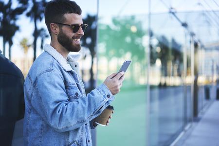 週末モダンな構築されたビジネス センターに近い selfie を取って街の散歩を楽しむ粋なカジュアル ルックに身を包んだ魅力的なひげを生やした男性