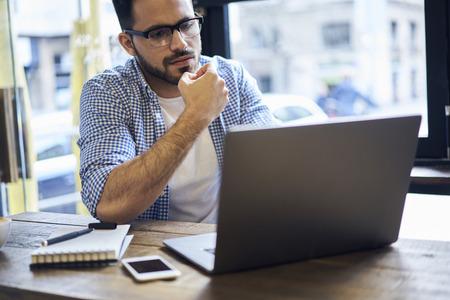 열심히 일하는 소득의 비율을 비교하는 온라인 데이타베이스에있는 재정적 인보고를 검사하고있는 동안 성공적인 브레인 스토밍의 사려 깊은 남성 경