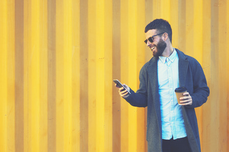 Handsome bearded male hipster making photo for blog sharing positive emotions feeling excited by sunny morning while walking to work with cup of coffee