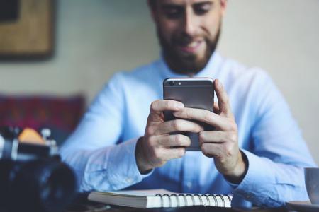 Jongelui die gebaarde mannelijke fotograaf glimlachen die online spelen speelt die moderne die smartphone gebruiken met 5G draadloos Internet wordt verbonden die niveaus voltooien