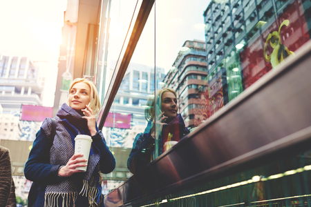 megapolis: Young female blonde hipster having city tour traveling in China calling to tourist center agency using smartphone and mobile coverage in roaming