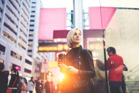 Mindful aantrekkelijke blonde met trendy korte kapsel wachten op gids om te kijken naar Hong Kong stadsplanning sightseeing tour in de ochtend