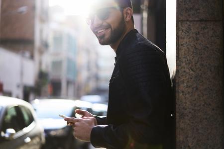 ハンサムな若い男で、路上でインターネット通信について広告コピー スペース携帯で立ったままカメラを笑顔で眼鏡をスタイリッシュな服とトレン 写真素材