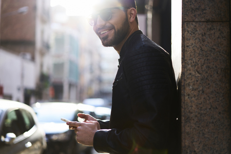 Handsome young man dressed in stylish clothing and trendy sun glasses with smile looking to the camera while standing with cellular on street, copy space for advertising  about internet communication