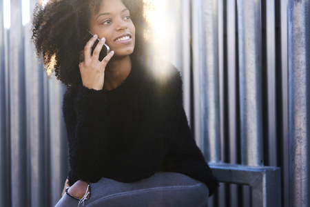 media gadget: Female afro American teen hipster arranging meeting with friends and workshop in modern coffee shop while having conversation via smartphone with manager