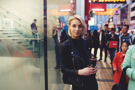 go inside: Attractive female blonde traveler in trendy black leather jacket and short haircut having city tour in Asian megalopolis spending leisure in Chinese