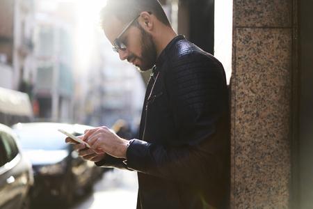 若いカジュアルな服を着たビジネスマンは現代的な新聞スマート フォン向けアプリの金融ニュースを読みます。男性の観光客が海外不慣れな新しい 写真素材