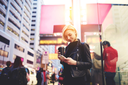 Talented female travel blogger typing text of publication about Chinese business center posting multimedia files in social network Stok Fotoğraf