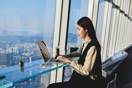 Woman successful freelancer is using laptop computer to make money on the Internet, while is sitting in modern co-working space near window with view of metropolitan city during her trip to China