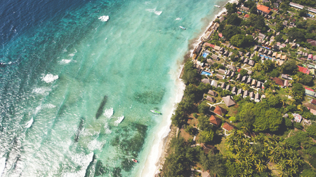 Top view aerial drone photo of stunning colored sea beach with crystalline water fringed with swaying tropical palms and leafy trees. Incredibly beautiful blue ocean meet with powder-white seashore Фото со стока